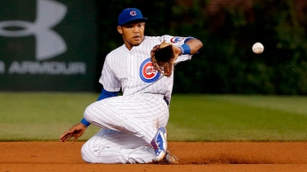 CHICAGO, IL - JUNE 14: Addison Russell #22 of the Chicago Cubs makes a sliding catch on a pickoff attempt thrown by David Ross (not pictured) during the fifth inning at Wrigley Field on June 14, 2015 in Chicago, Illinois.  (Photo by Jon Durr/Getty Images)
